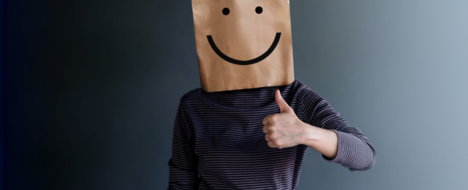 person with paper back over head with smiling face